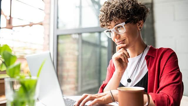 Busy young elegant woman in eyeglasses looking at laptop display